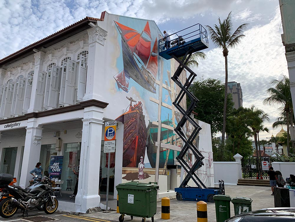 Jaba on a boom lift painting the top of the ship and completing his mural in Jan 2021